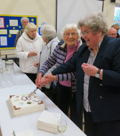 Barbara Wootton, on the left in the pink jumper, and Rita Ford cut the cake