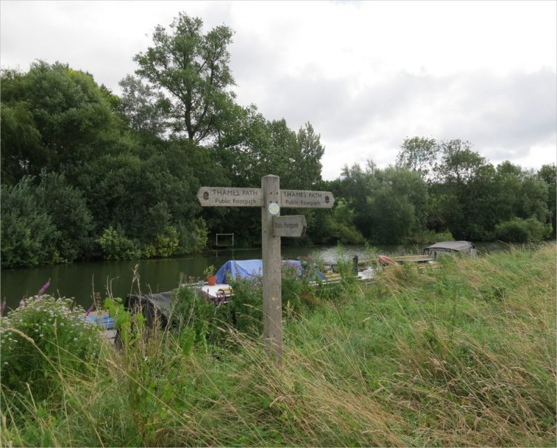 Wooden Thames Path signpost on the river bank at Radley near the Radley College boathouse